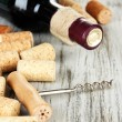 Corkscrew with wine corks and bottle of wine on wooden table close-up — Stock Photo #28652043