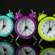 Colorful alarm clock on dark grey background — Stock Photo