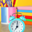 Blue alarm clock on table on yellow background — Stock Photo