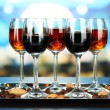 Stock Photo: Glasses of liquors with almonds and coffee grains, on tray, on bright background