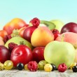 Stock Photo: Assortment of juicy fruits, on wooden table, on bright background
