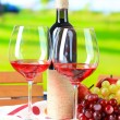 Glasses of wine on napkin on tray on wooden table on nature background — Stock Photo
