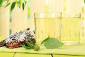 Verres de sève de bouleau sur table en bois vert — Photo