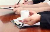 Gros plan des mains de femme d'affaires avec une tasse de café pendant le travail d'équipe — Photo