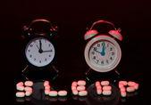 Old style alarm clocks and pills, on dark background — Stock Photo