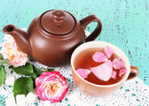 Kettle and cup of tea from tea rose on board on napkin on wooden background — Stock Photo