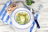 Soup in plate on napkin on wooden board on table — Stock Photo