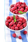 Ripe sweet raspberries in bowls, isolated on white — Stock Photo