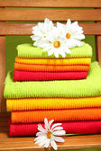 Towels and flowers on wooden chair on green background — Stock Photo