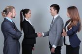 Business colleagues introducing with handshake, on grey background — Stock Photo