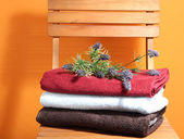 Towels and flowers on wooden chair on orange background — Stock Photo
