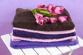 Handtücher und blumen auf holzstuhl auf lila hintergrund — Stockfoto