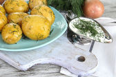 Boiled potatoes on platen on wooden board near napkin on wooden table — Stock Photo