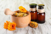 Medicine bottles and calendula flowers on wooden background — Stockfoto