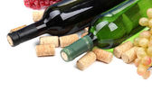 Bottles of wine, grapes and corks, isolated on white — Stock Photo