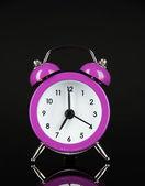 Purple alarm clock on dark grey background — Stock Photo