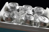 Metal cans of beer with ice cubes in mini refrigerator, close up — Stock Photo