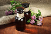 Medicine bottles with clover flowers on wooden table with burlap — Stock Photo
