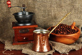 Metal turk and coffee mill on burlap background — Stock Photo