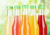 Bottles with tasty drinks on bright background — Stock Photo