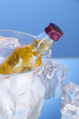 Minibar bottles in bucket with ice cubes, on color background — Stock Photo