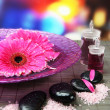 Gerbera flowers on water and spa stones on bamboo mat — Stok fotoğraf