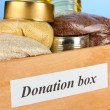 Donation box with food on blue background close-up — Stock Photo #28767125