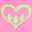 Green cut out paper heart with people inside, on color background — Stock Photo #28767365