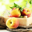 Stock Photo: Ripe sweet peaches in wooden crate, outside
