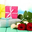Beautiful roses and presents, on bright background — Stock Photo