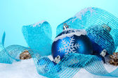 Beautiful blue Christmas balls and cones in snow on blue background — Foto de Stock