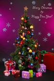 Ingericht kerstboom met geschenken op paarse achtergrond — Stockfoto