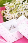 Beautiful box with wedding ring on purple background — Stock Photo