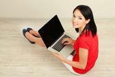 Vacker ung kvinna sitter med anteckningsboken i rum — Stockfoto