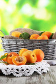 Apricots in basket on napkin on wooden table on nature background — Stock Photo