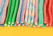 Sweet jelly candies on yellow backgroun — Stock Photo