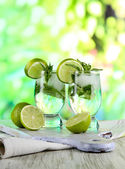 Glasses of cocktail with ice on board on napkin on wooden table on nature background — Stock Photo