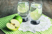 Glasses of cocktail with lime on napkin on dark wooden table — Stock Photo