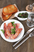 Bacon on plates on wooden table — Stock Photo