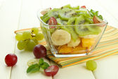 Tasty fruit salad in glass bowl, on white wooden table — Stock Photo