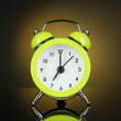 Green alarm clock on dark yellow background — Stock Photo
