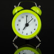 Green alarm clock on dark grey background — Stock Photo