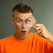 Young man looking through magnifying glass on grey background — Stock Photo