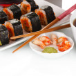 Delicious sushi on plate, chopsticks, soy sauce, fish and shrimps isolated on white — Stock Photo #28796217