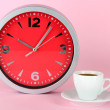 Cup coffee and clock on pink background — Stock Photo