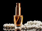 Profumo di donna bella bottiglia e perline, su sfondo nero — Foto Stock