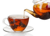 Glass teapot pouring black tea into cup isolated on white — Stock Photo