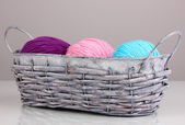 Bright threads for knitting in basket on grey background — Stock Photo