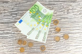 Euro banknotes and euro cents on grey glass background — Stock Photo