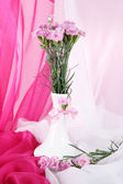 Many small pink cloves in vase on light fabric background — Stock Photo